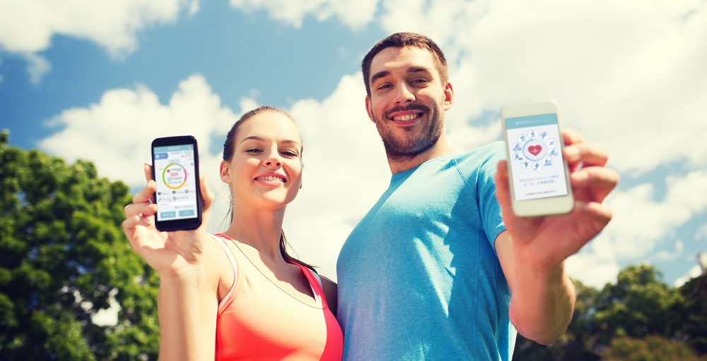 fitness, sport, training, technology and lifestyle concept - two smiling people with smartphones outdoors